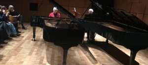 Two pianos side by side with two performers