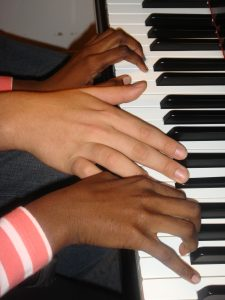 Two hand, one tan and one brown on the piano